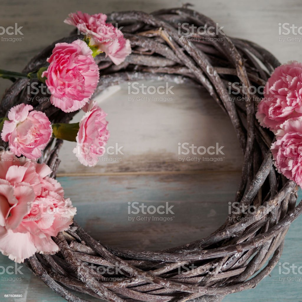 Round wreath of dry branches with pink flowers, on blue turquoise wooden background, place for text. Springtime and revival concept stock photo