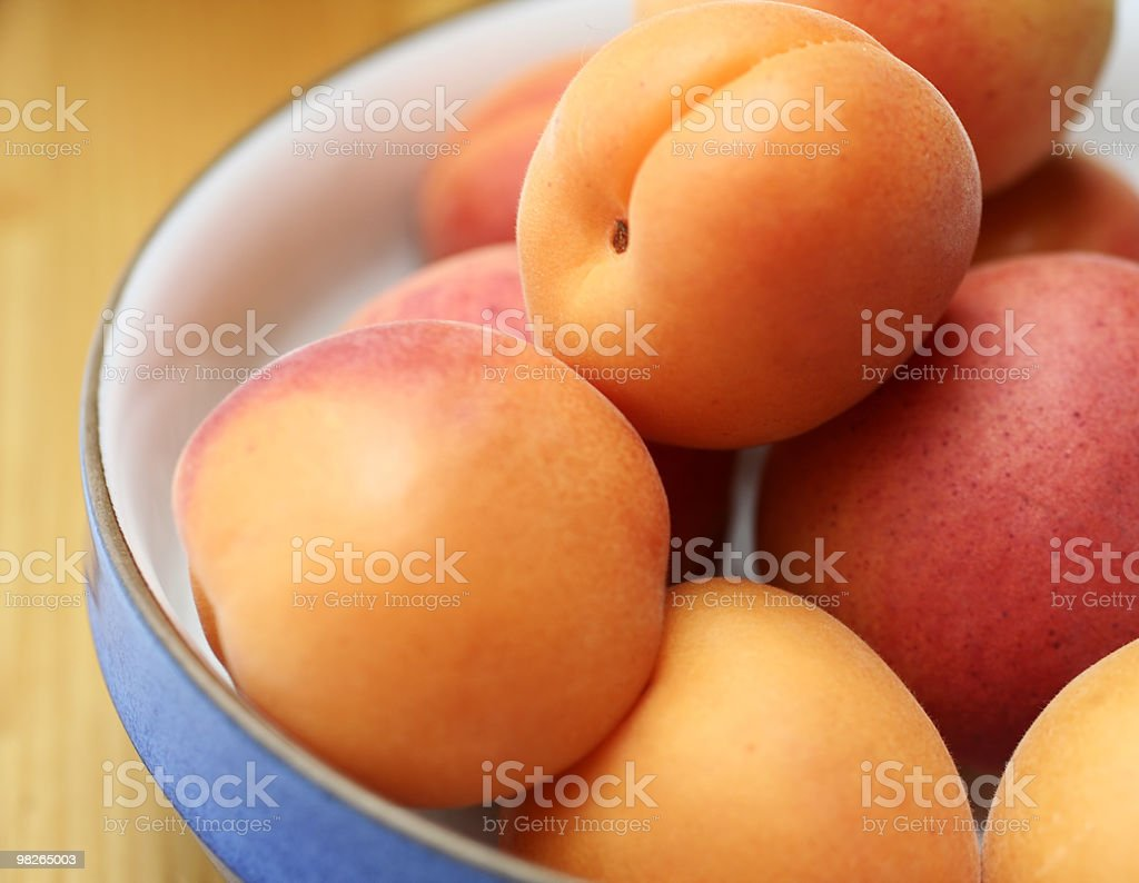 Rounded orange and pink apricots sitting in a bowl royalty-free stock photo