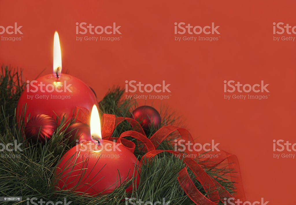 Rounded red candles and christmas baubles on green fir . royalty-free stock photo