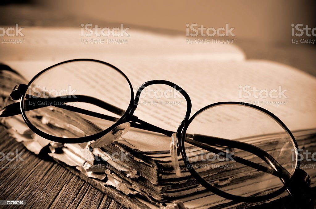 round-framed eyeglasses and old book, in sepia toning stock photo