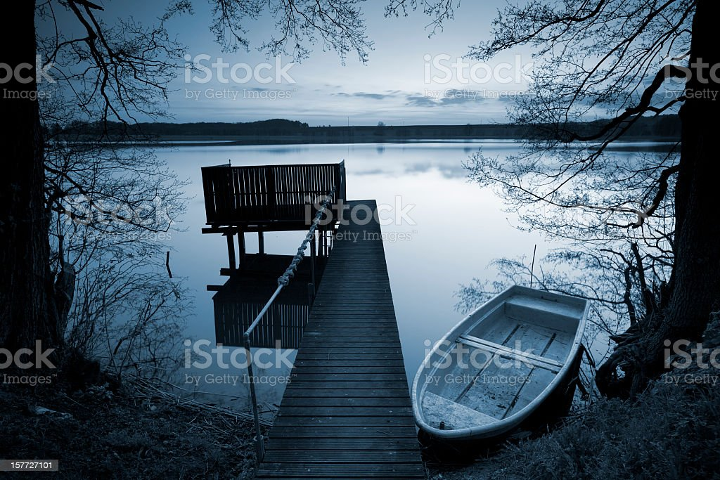 Row Boat and Dock on Calm Lake framed by Trees stock photo