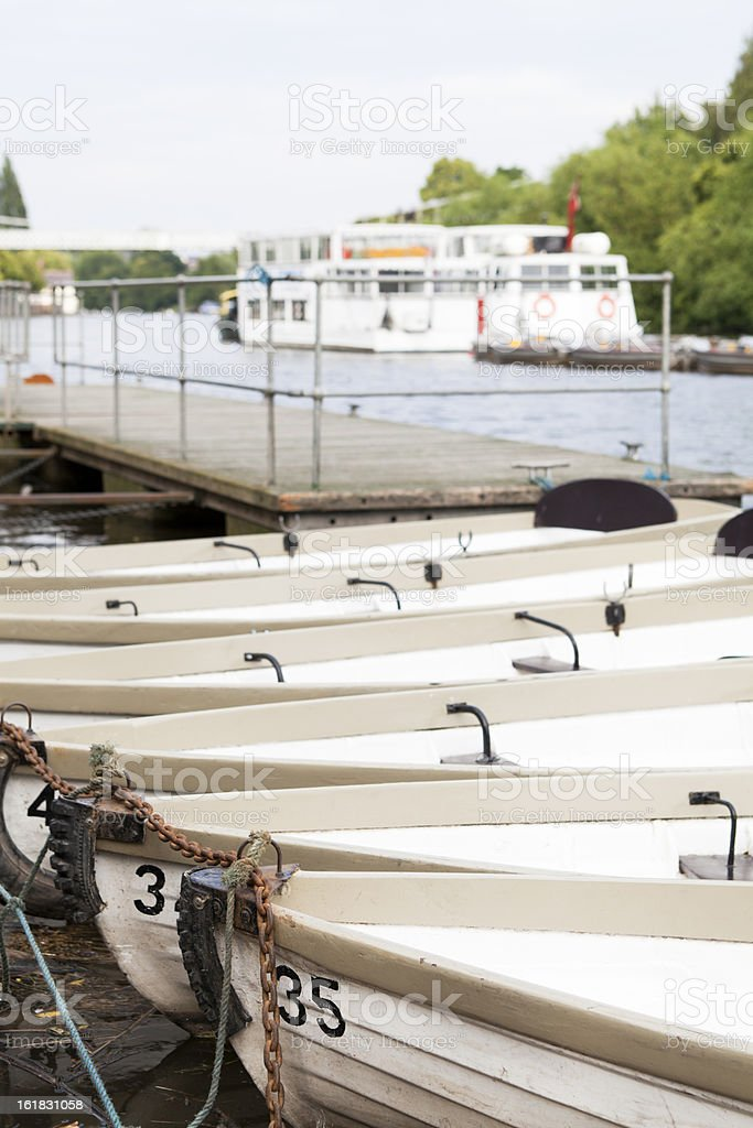 row boats tied up along side a river in England stock photo