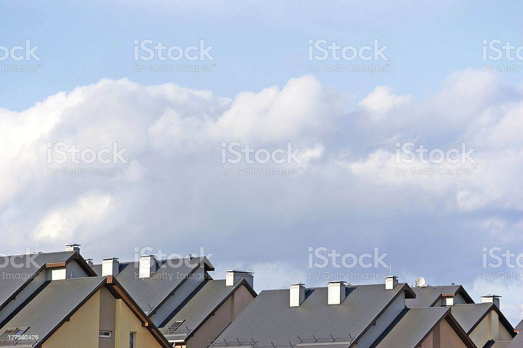 Row house roofs, condo rooftop panorama and bright summer cloudscape royalty-free stock photo