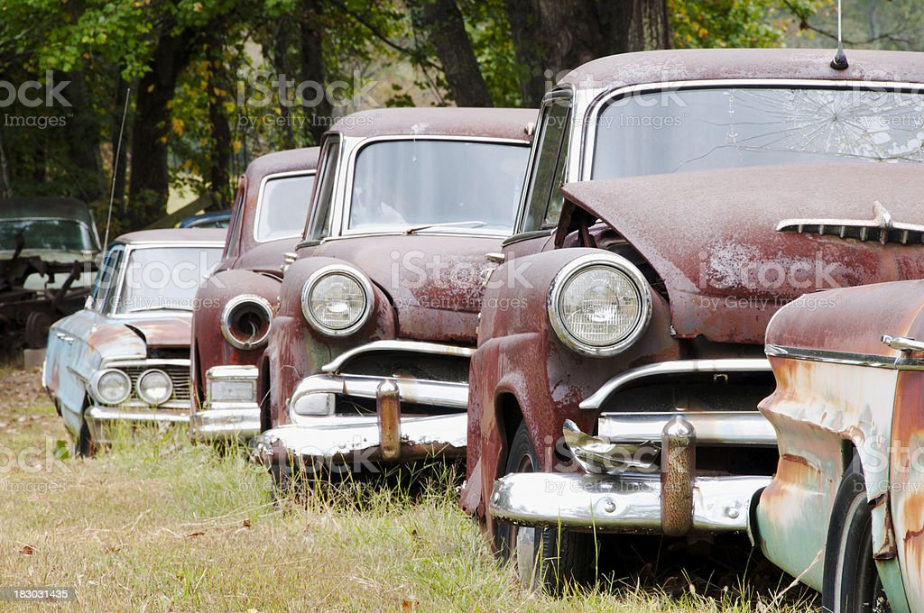 Row of abandoned rusted cars stock photo