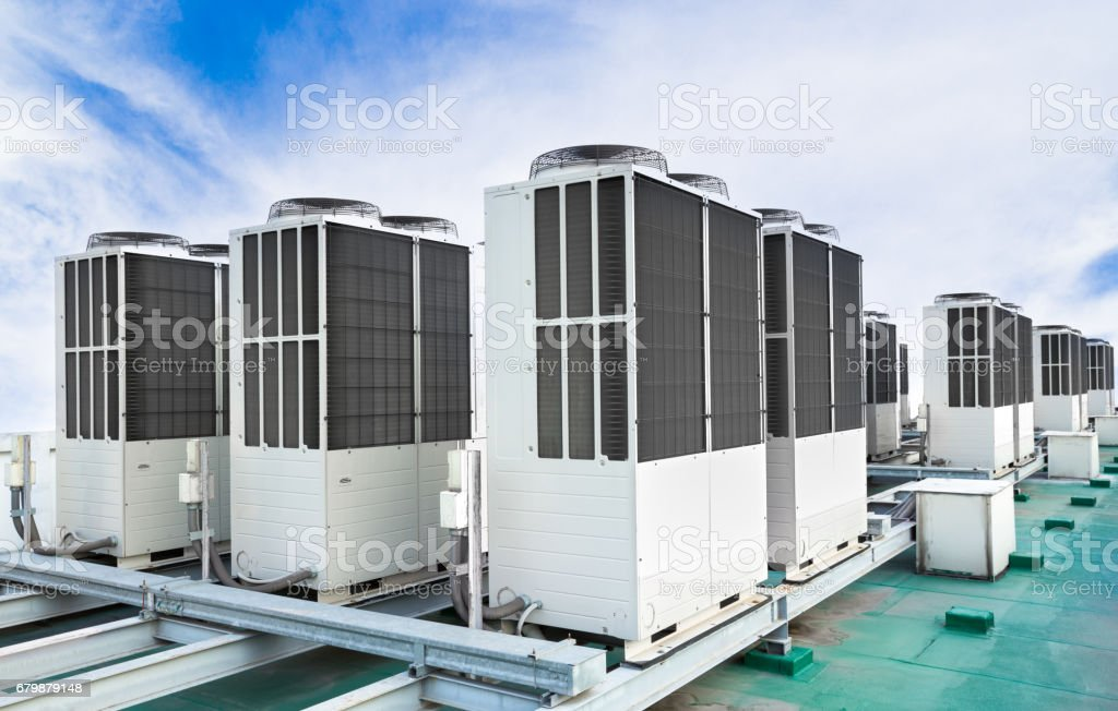 Row of air conditioning units on rooftop with blue sky stock photo