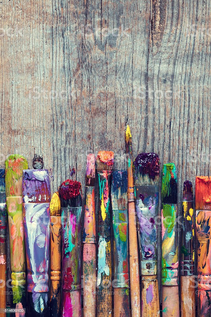 Row of artist paint brushes closeup on wooden background stock photo