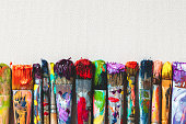 Row of artist paintbrushes closeup on canvas.