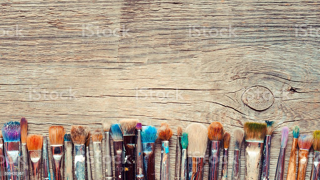 Row of artist paintbrushes closeup on old wooden background stock photo