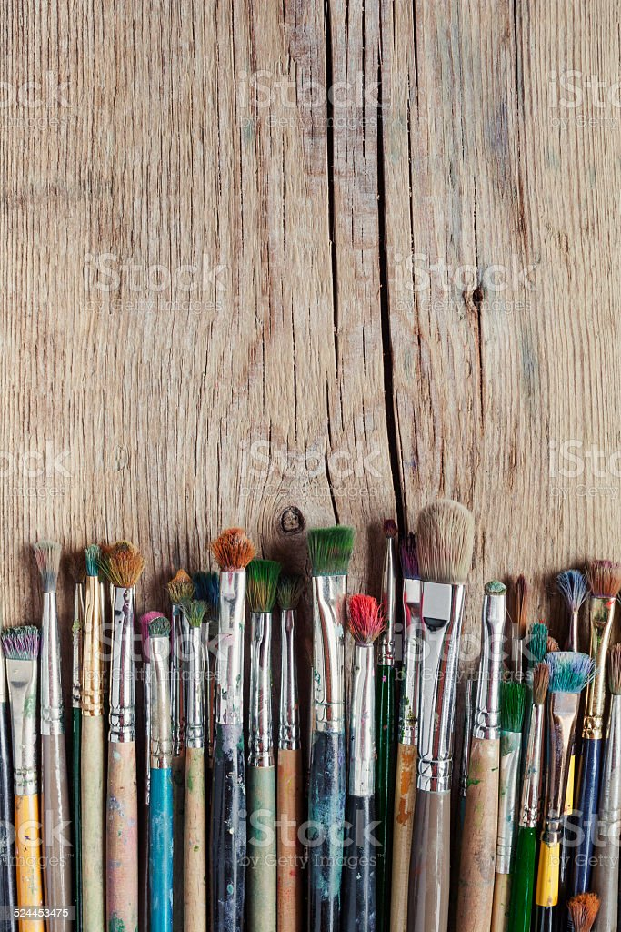 row of artist paintbrushes on old wooden table stock photo