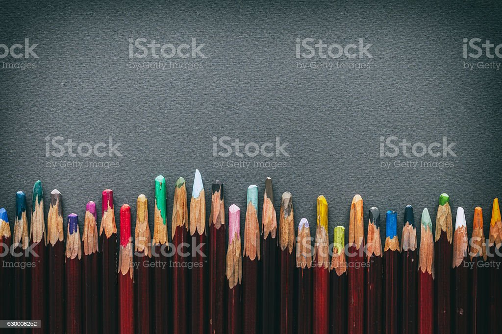 Row of artist pastel pencils on pastel paper sheet. stock photo