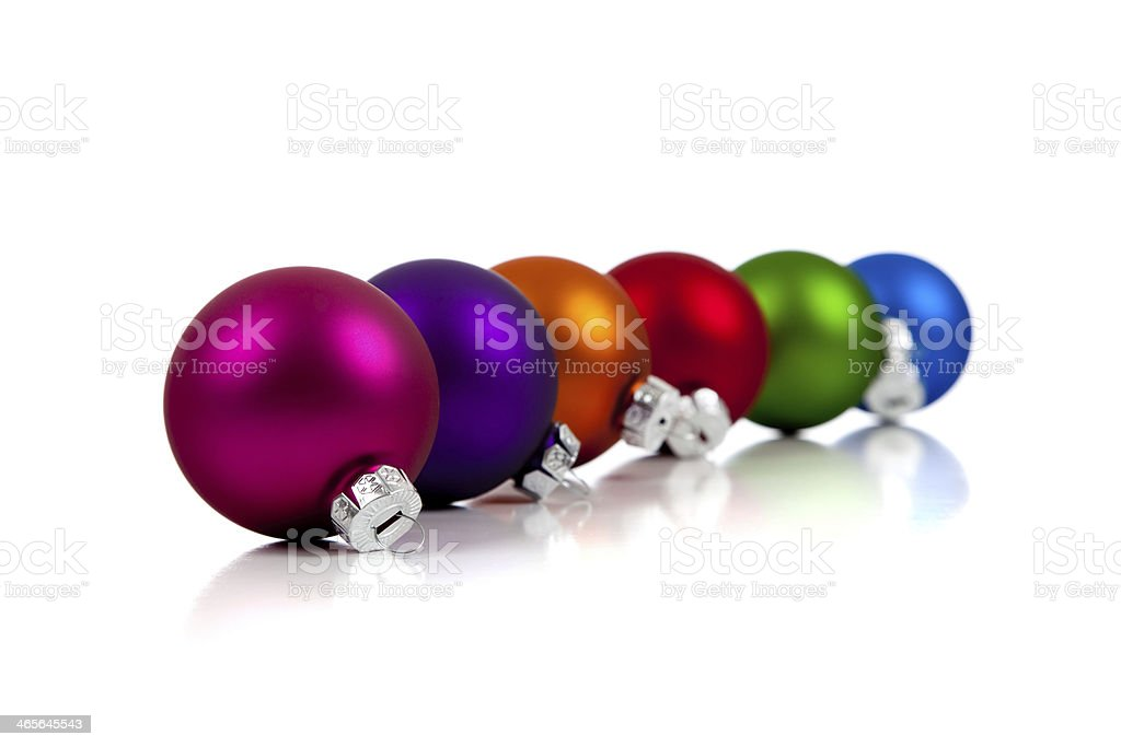 Row of assorted Christmas ornaments/baubles on white stock photo