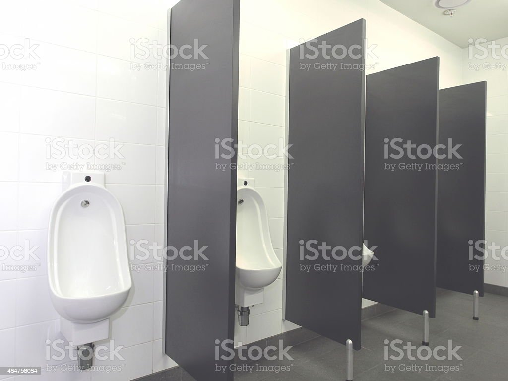 Row of automatic flush Urinals in a pristine industrial lavatory stock photo
