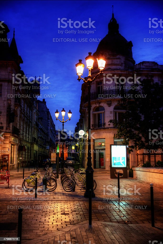 Row of bicycles in quiet street Orleans France at dusk stock photo