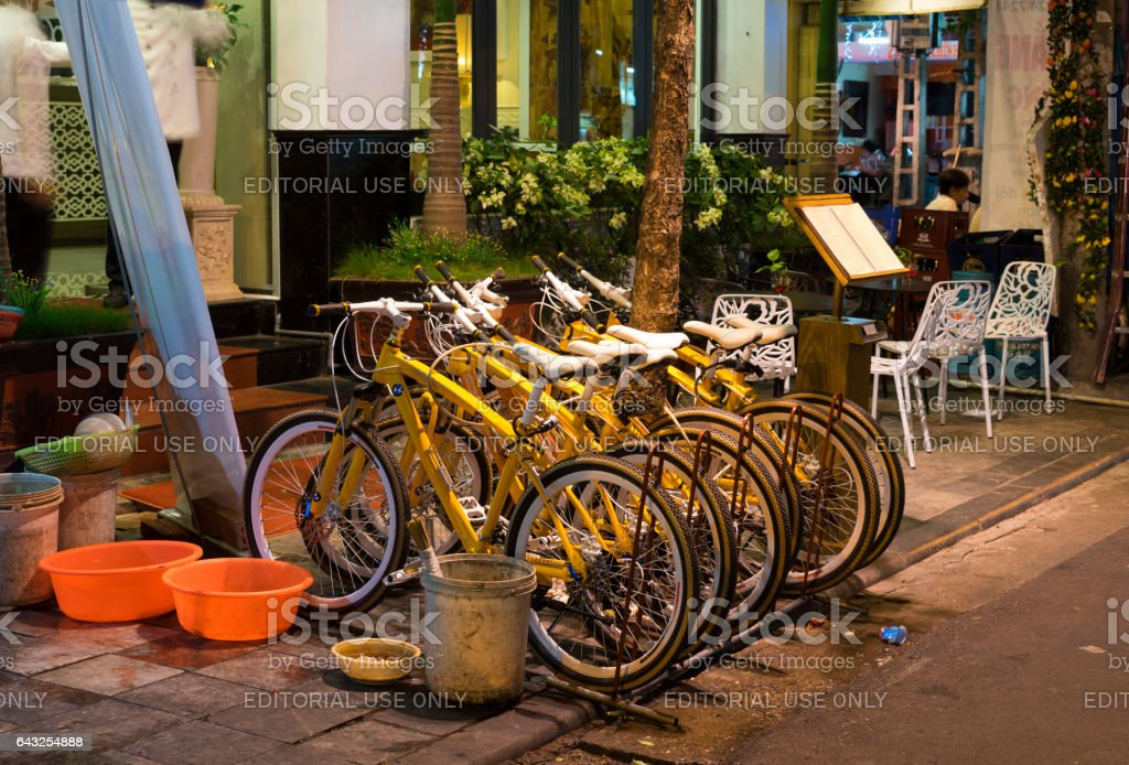 Hanoi, Vietnam - Nov 2, 2014: Row of bikes for rent on Ma May street at night, old quarter of Hanoi stock photo
