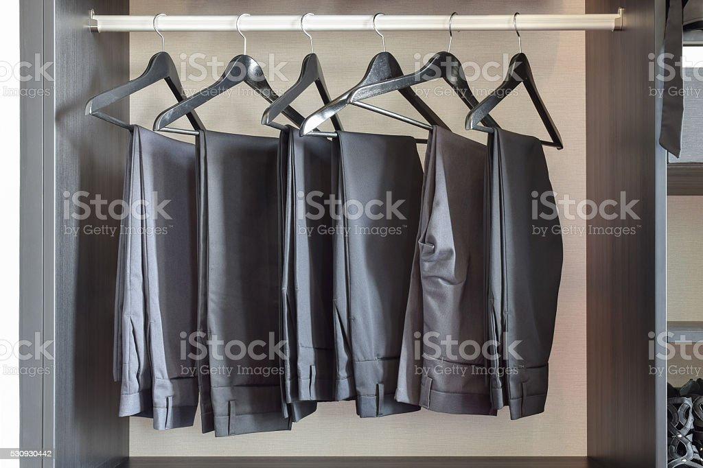 row of black pants hangs in wardrobe at home stock photo