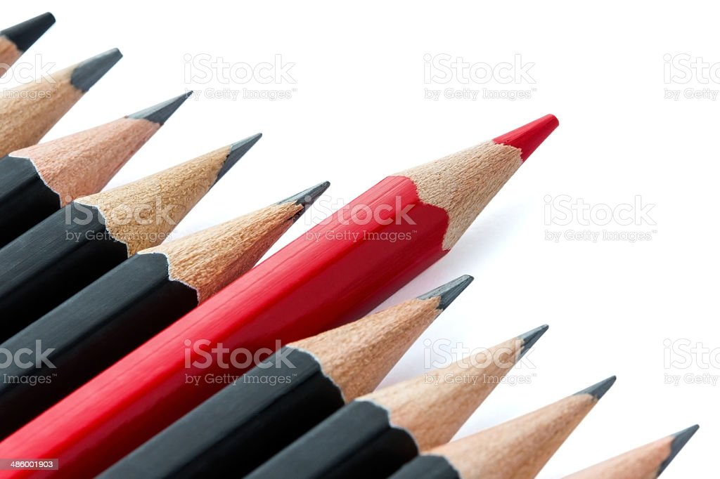 Row of black pencils with one red pencil in middle stock photo