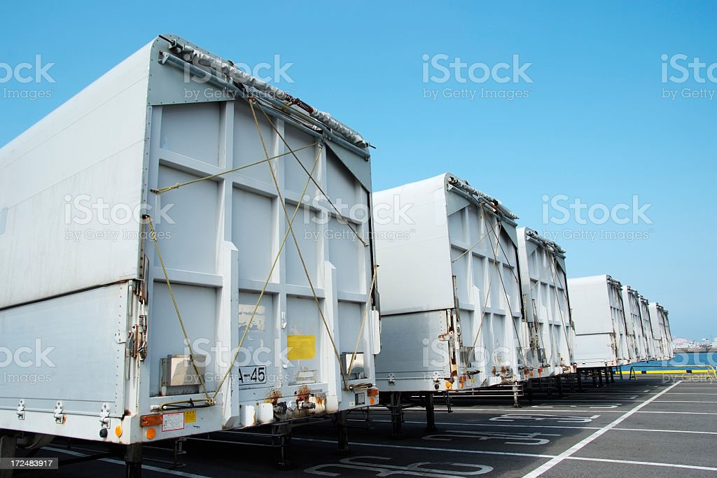 Row of blank silver semi truck trailers against blue sky royalty-free stock photo