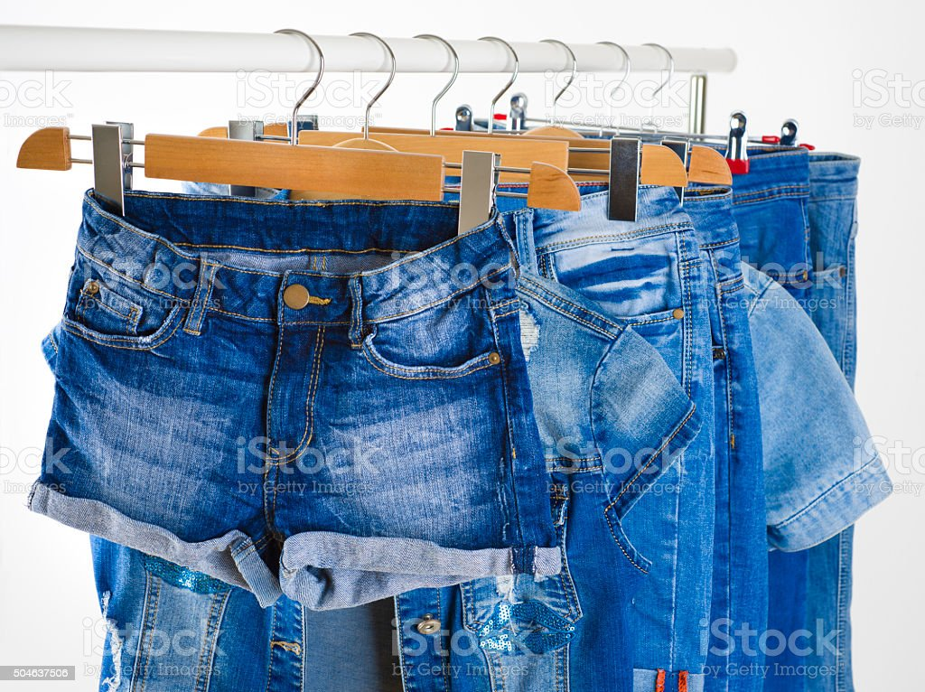 Row of blue jeans clothes on hangers in a shop stock photo
