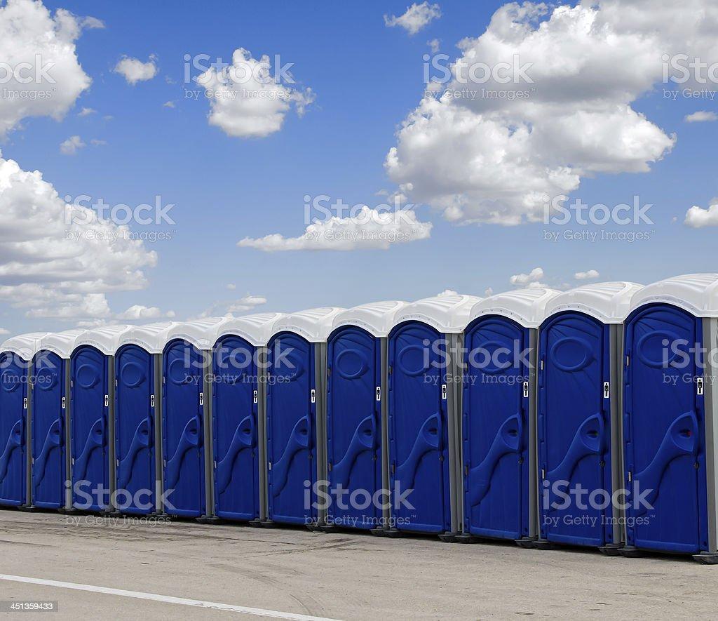 Row of blue portable toilets stock photo