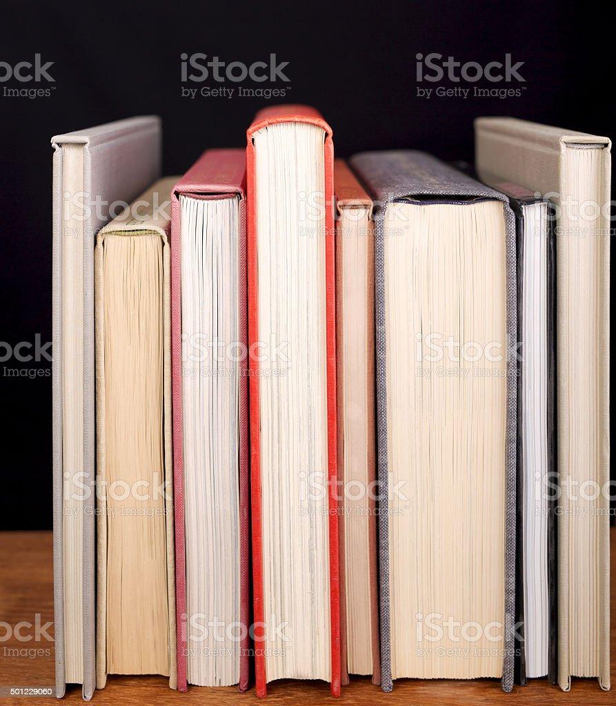 Row of books on bookshelf. Black background. stock photo