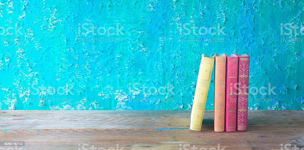 row of books on green grungy background stock photo