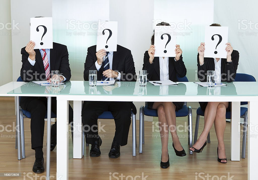 Row of businesspeople with question marks stock photo