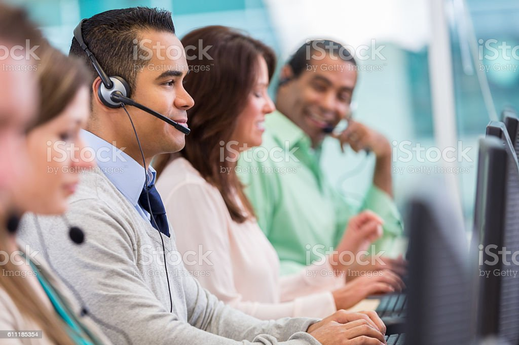 Row of call center employees assist customers stock photo
