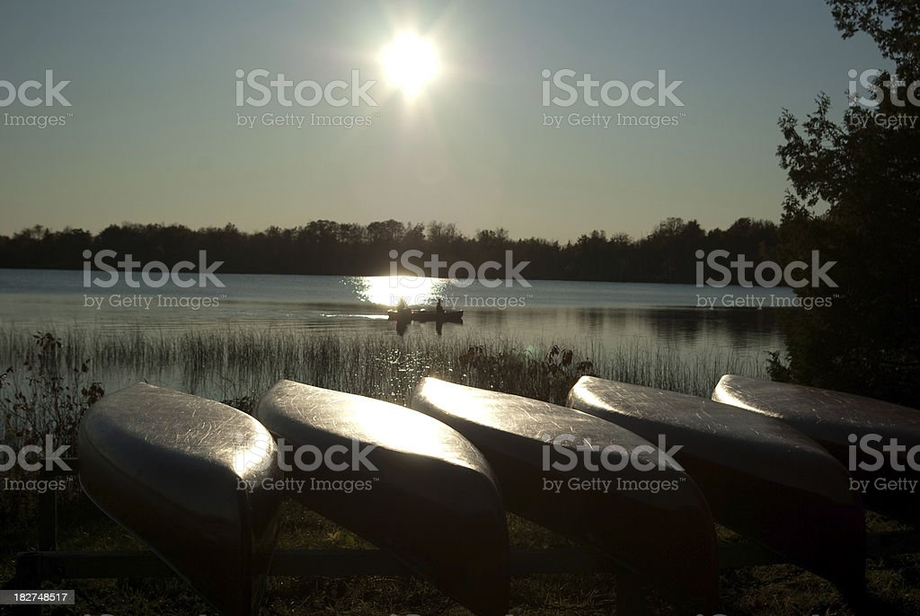 Row of Canoes Overlooking Two People in Canoe at Dusk royalty-free stock photo