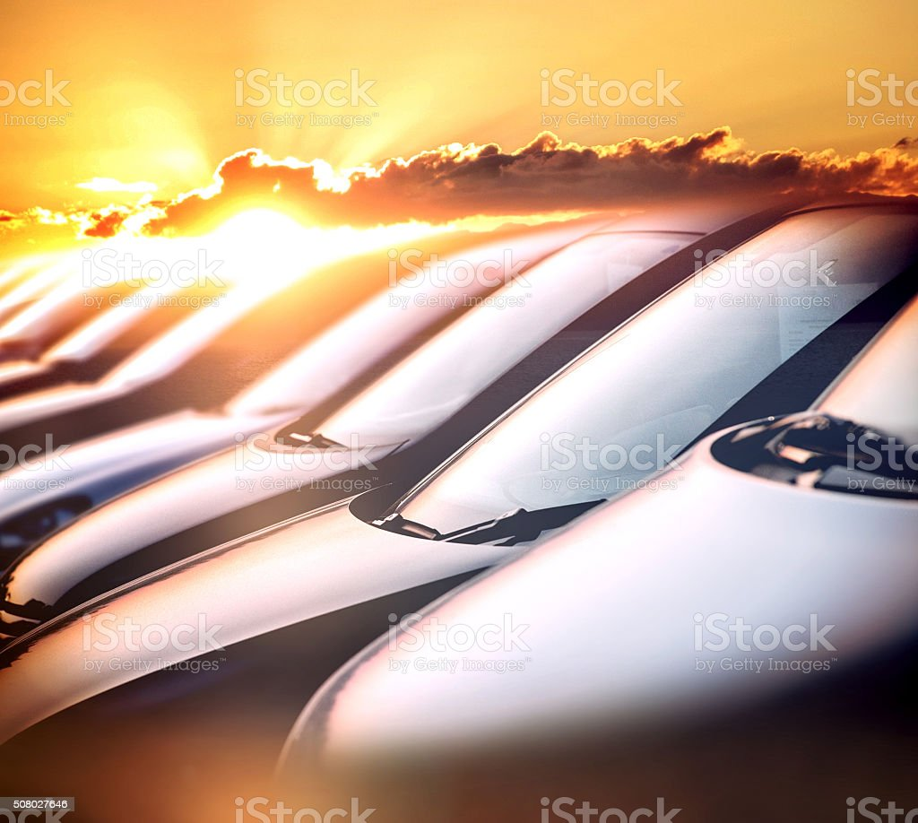 Row of cars against bright sunset stock photo