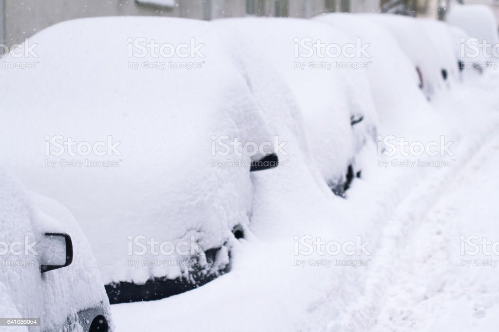 row of cars covered in snow in a parking lot stock photo