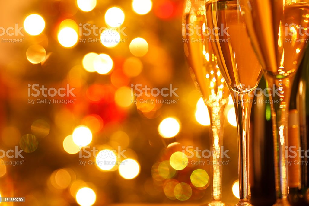 Row of champagne glasses in front of blurred Christmas lights royalty-free stock photo