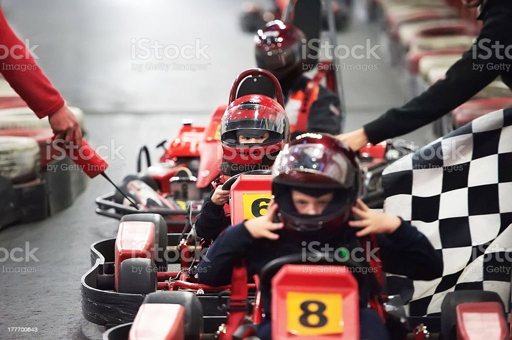 Row of children in go-karts with helmets ready for a race stock photo
