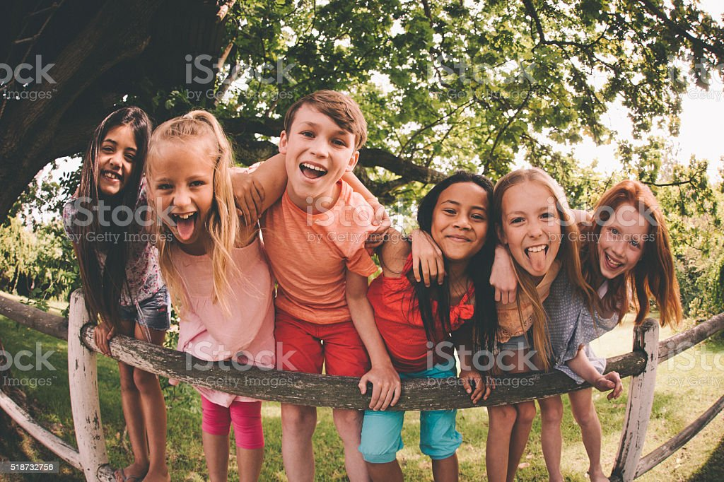 Row of children on a fence in a park laughing stock photo