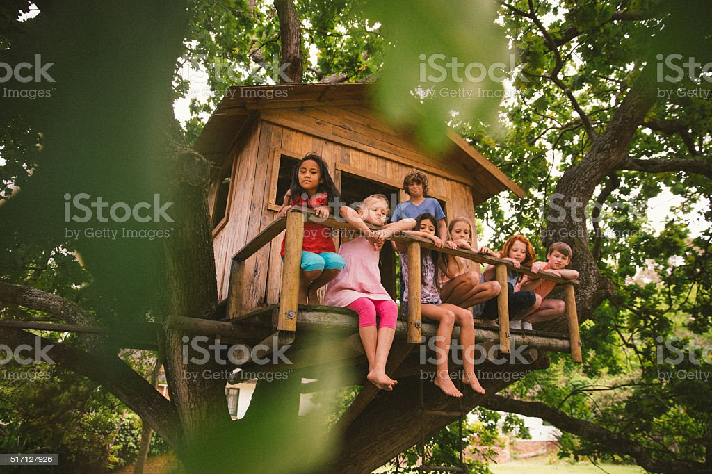 Row of children sitting on a rustic wooden treehouse porch stock photo