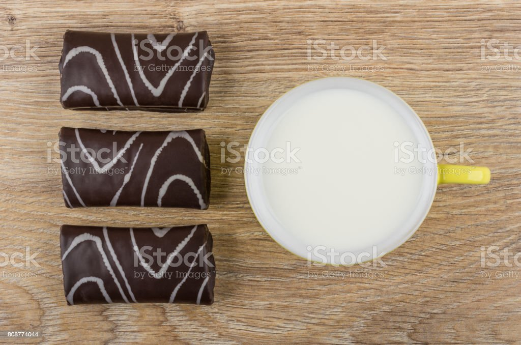 Row of chocolate swiss rolls, cup with milk on table stock photo
