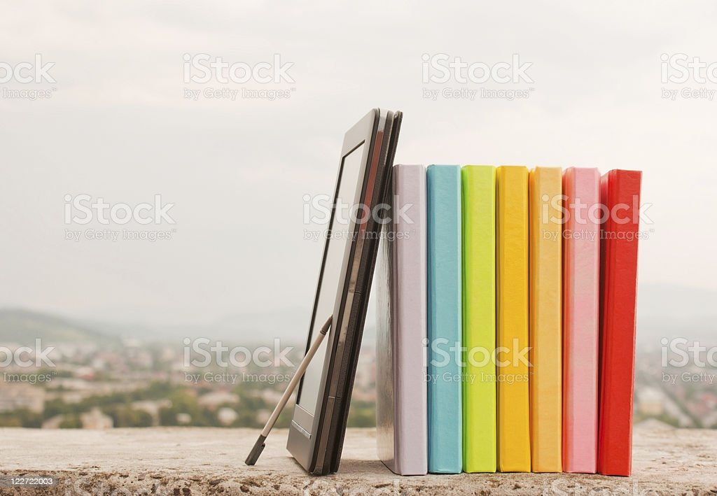 Row of colorful books with electronic book reader royalty-free stock photo