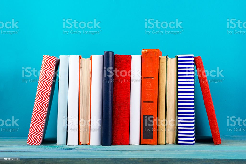 Row of colorful hardback books, open book on blue background stock photo