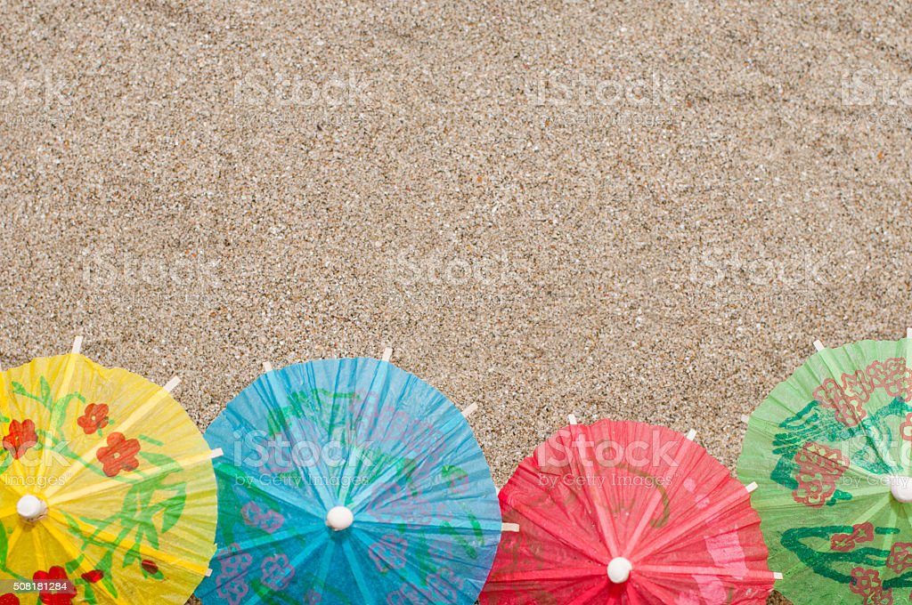 Row of colorful little cocktail umbrellas on sea sand stock photo