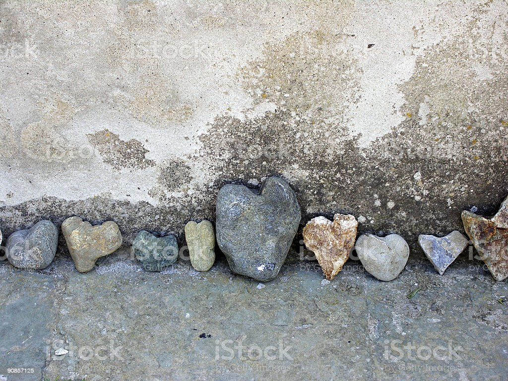 Row of colorful rocks shaped like hearts with big in middle stock photo