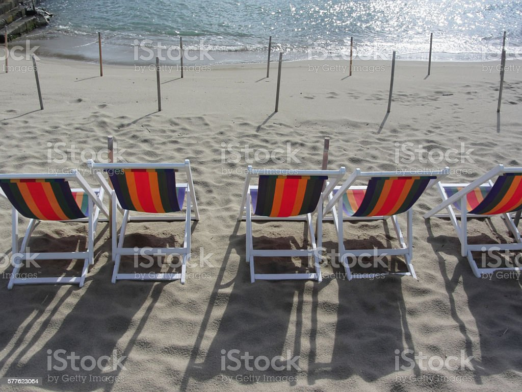 Row of colorful wooden chairs at sand beach stock photo