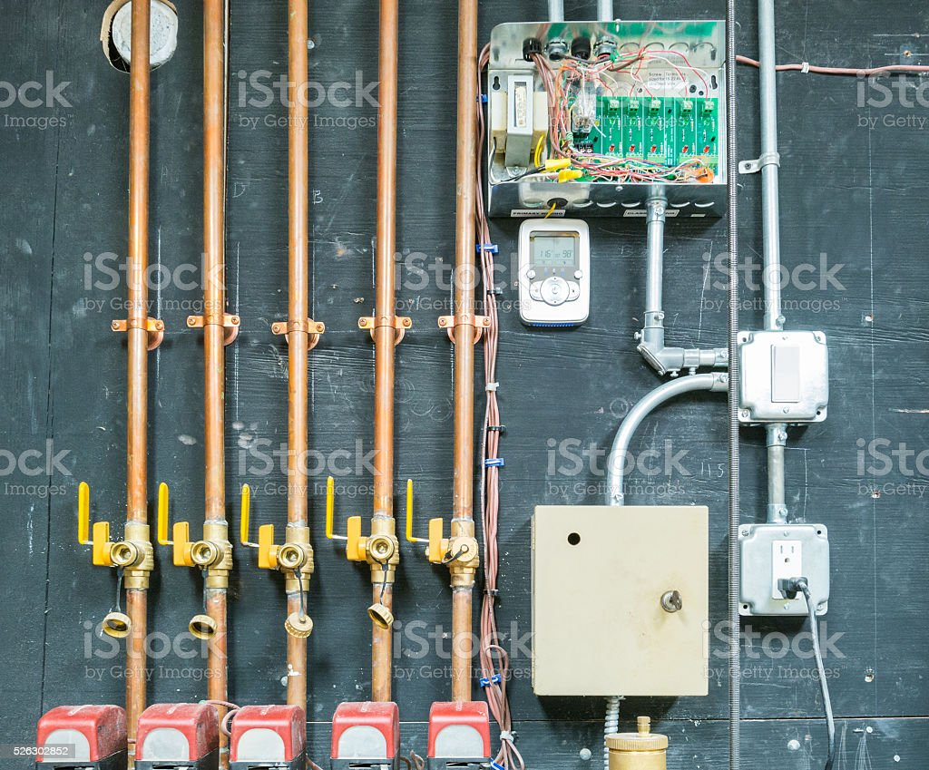 Row of copper pipes with control unit stock photo