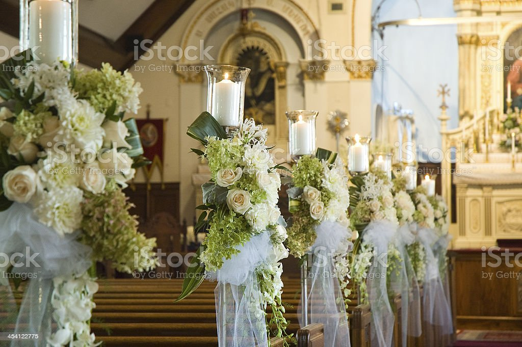 Row of cream wedding flowers with candles and white silk stock photo
