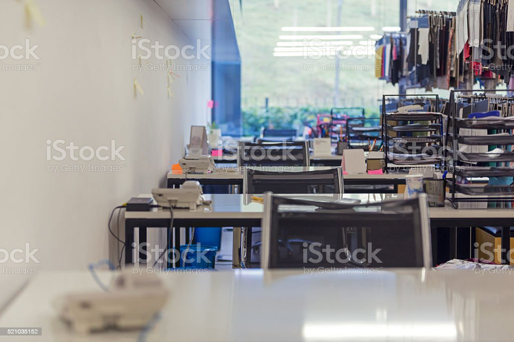 Row of desks in empty office stock photo
