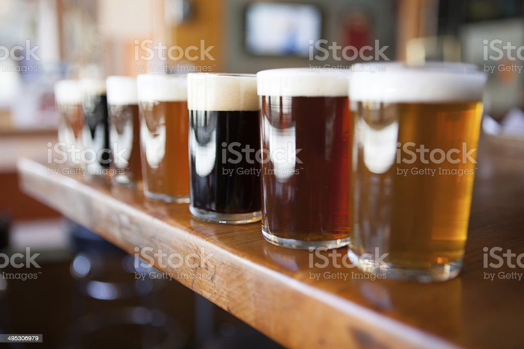 Row of different beers in glasses on a wooden bar stock photo
