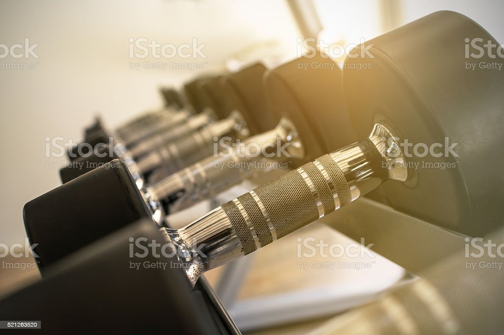 row of dumbbells in modern sports club stock photo