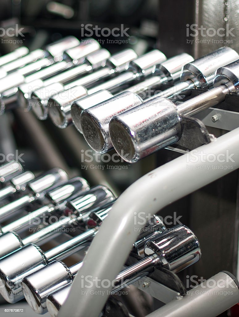 row of dumbbells neatly stacked on their stands stock photo
