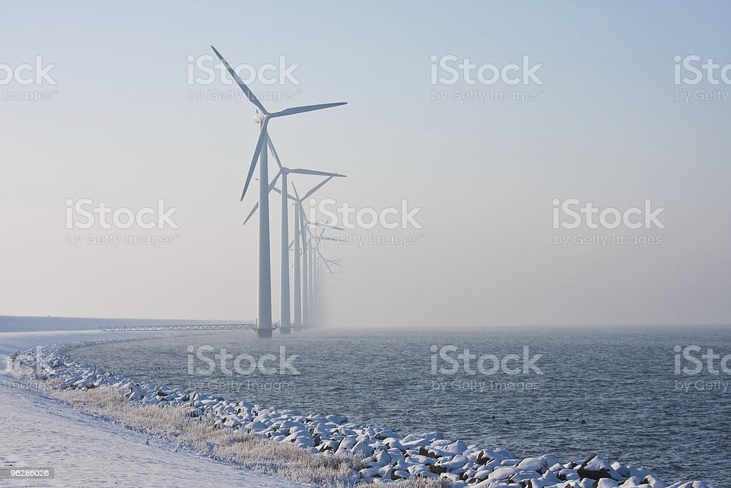Row of Dutch windmills disappearing in winter haze stock photo