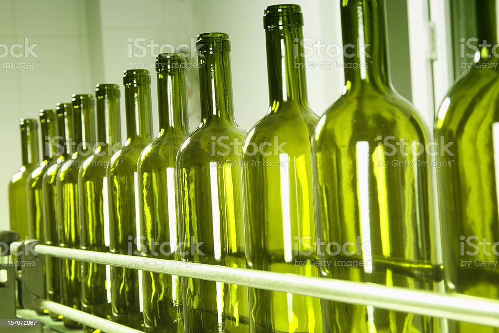 A row of empty green wine bottles on a conveyor belt stock photo