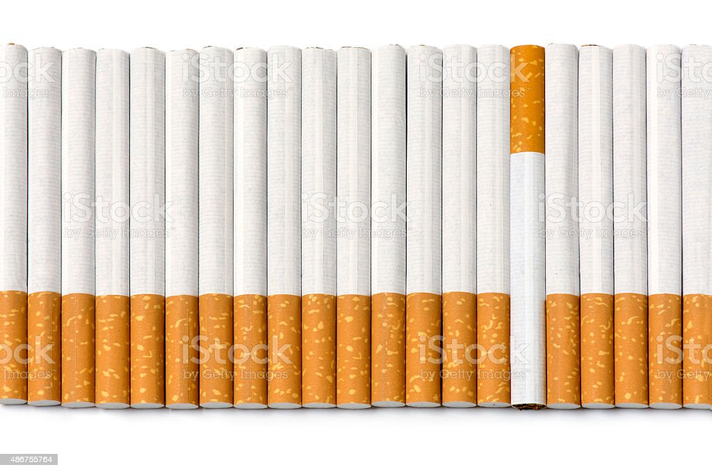 row of filter cigarettes, one is upside down, on white stock photo