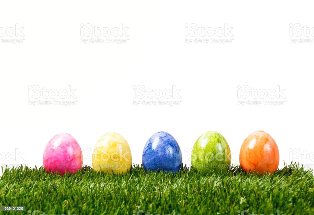 Row of five colorful easter eggs on green grass isolated stock photo